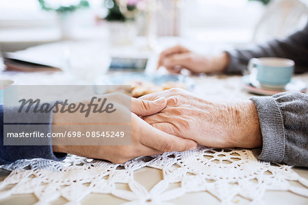Cropped image of caretaker consoling senior man at dining table Stock Photo - Premium Royalty-Free, Image code: 698-08545249