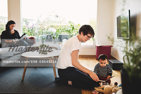 Mother and daughter playing with toys while woman using digital tablet at home Stock Photo - Premium Royalty-Free, Image code: 698-08545516