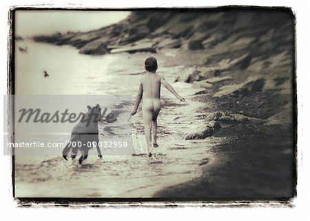 Back View of Nude Boy Running on Beach With Dog