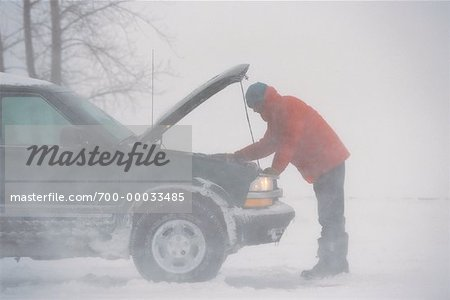 Man Looking Under Hood of Vehicle Outdoors in Winter Stock Photo - Rights-Managed, Image code: 700-00033485