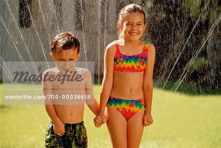 Boy and Girl in Swimwear, Playing In Sprinkler