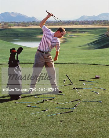 700-00048709em-Golfer-Breaking-Golf-Clubs-on-Golf-Course---