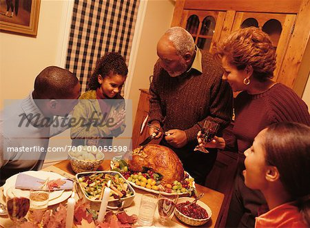 Grandfather Carving Turkey at Thanksgiving Dinner Table Stock Photo - Rights-Managed, Image code: 700-00055598