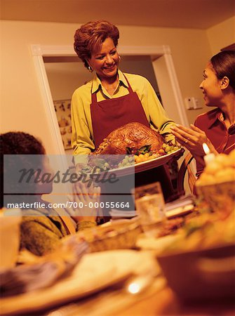 Grandmother Bringing Turkey to Thanksgiving Dinner Table Stock Photo - Rights-Managed, Image code: 700-00055664