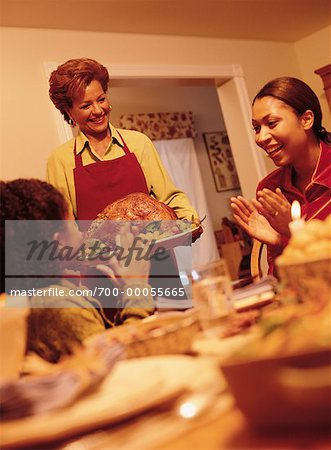Grandmother Bringing Turkey to Thanksgiving Dinner Table Stock Photo - Rights-Managed, Image code: 700-00055665