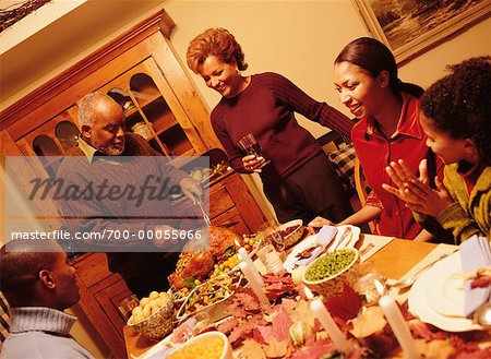 Grandfather Carving Turkey at Thanksgiving Dinner Table Stock Photo - Rights-Managed, Image code: 700-00055666
