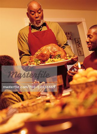 Grandfather Bringing Turkey to Thanksgiving Dinner Table Stock Photo - Rights-Managed, Image code: 700-00055669