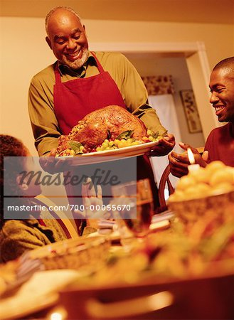 Grandfather Bringing Turkey to Thanksgiving Dinner Table Stock Photo - Rights-Managed, Image code: 700-00055670