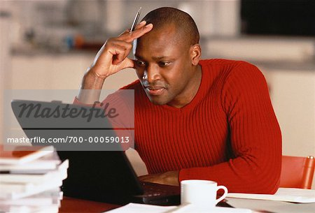 Man Sitting at Table Using Laptop Computer, Resting Head on Hand