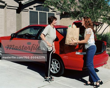 Daughter Handing Bag of Groceries To Mature Mother near Car Stock Photo - Rights-Managed, Image code: 700-00062279