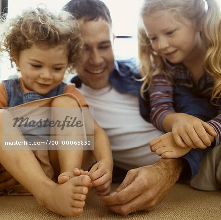 Father and Daughters Sitting on Ground, Tickling Daughter's Feet