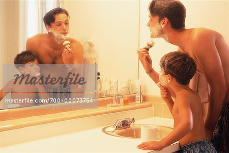 Father and Son Shaving in Bathroom Mirror
