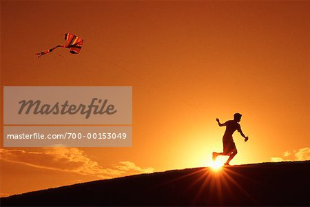 Silhouette of Boy Flying Kite At Sunset