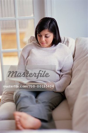 Woman Reading on Sofa Stock Photo - Rights-Managed, Image code: 700-00193404