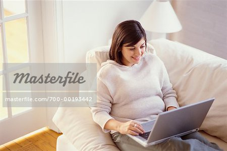 Woman on Sofa Using Laptop Stock Photo - Rights-Managed, Image code: 700-00193442