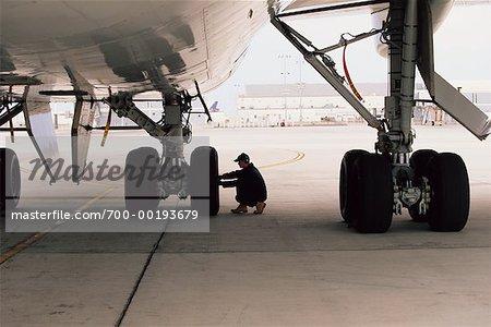 Aircraft Worker Checking Landing Gear