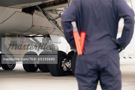 Airline Worker Looking at Airplane