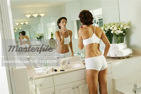 Woman Applying Make up in Bathroom   Stock Photo. Woman Applying Make up in Bathroom   Stock Photo   Masterfile