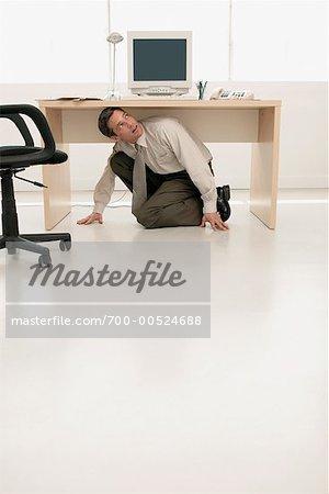 Businessman hiding under desk stock photo premium rights managed