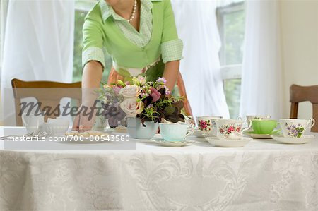 Woman Setting Table with Vintage Teacups