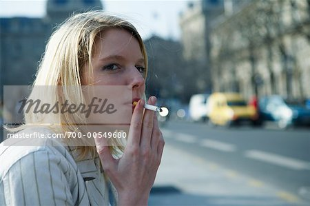 Woman Sitting on Curb Smoking Cigarette, Paris, France