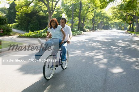 Couple Riding on Bicycle Together, Woman Sitting on Handlebars