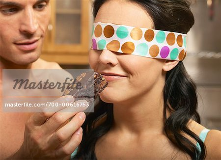 Man Feeding Blindfolded Woman a Brownie Stock Photo - Rights-Managed, Image code: 700-00616753