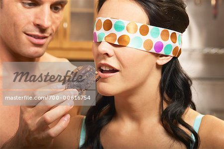 Man Feeding Blindfolded Woman a Brownie Stock Photo - Rights-Managed, Image code: 700-00616754