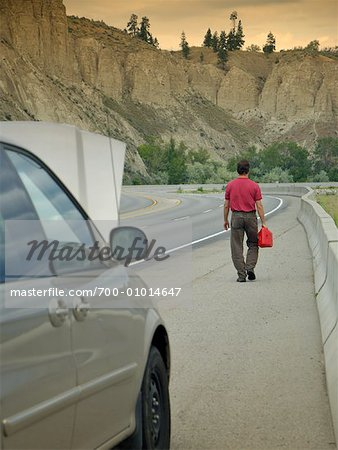Man Walking on Road, Carrying Gas Can Stock Photo - Rights-Managed, Image code: 700-01014647