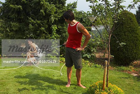 Man Spraying Woman With Hose