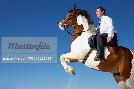 Horse Rearing with Businessman on Its Back Stock Photo - Rights-Managed, Image code: 700-01185194
