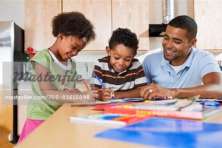 Children Doing Homework in Kitchen with Father