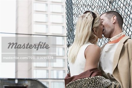Couple Leaning Against Fence Kissing Stock Photo - Rights-Managed, Image code: 700-01695228