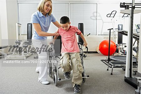Physiotherapist Helping Boy out of Wheelchair Stock Photo - Rights-Managed, Image code: 700-02071749