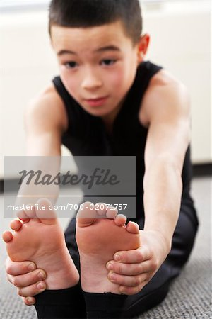 Boy Sitting on Floor Stretching Stock Photo - Rights-Managed, Image code: 700-02071757