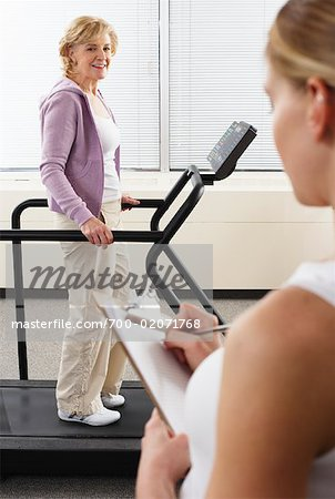 Woman using Treadmill with Physiotherapist Checking Progress Stock Photo - Rights-Managed, Image code: 700-02071768