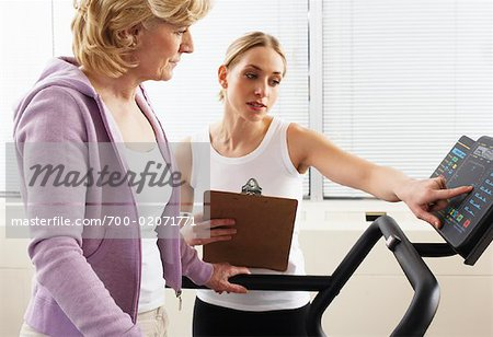 Woman using Treadmill with Physiotherapist Checking Progress Stock Photo - Rights-Managed, Image code: 700-02071771