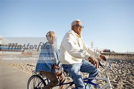 Seniors Riding Tandem Bicycle at Beach, Santa Monica Pier, Santa Monica, California, USA