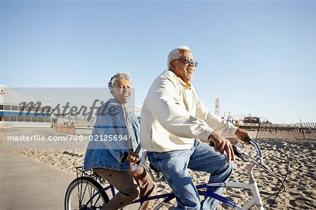 Seniors Riding Tandem Bicycle at Beach, Santa Monica Pier, Santa Monica, California, USA