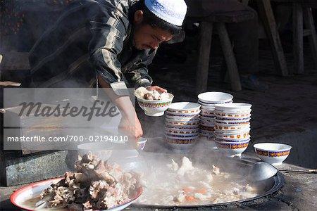 Man Preparing Food at Sunday Market, Kashgar, Xinjiang Autonomous Region, China