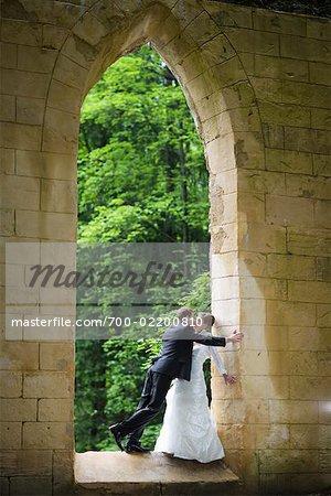 Groom Kissing Bride in Building Opening, Chamonix, Haute-Savoie, France