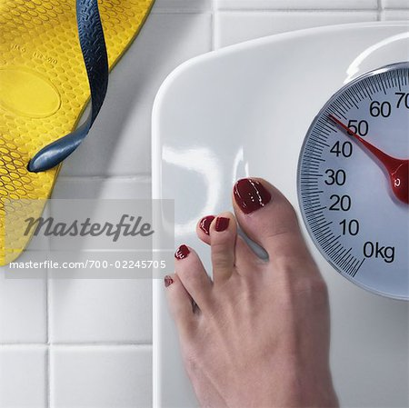 Woman Standing on Scale, Crossing Toes For Luck Stock Photo - Rights-Managed, Image code: 700-02245705
