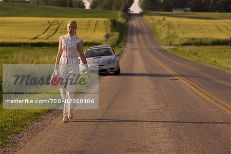 Woman Walking Along Country Road, Carrying Gas Can Stock Photo - Rights-Managed, Image code: 700-02260106