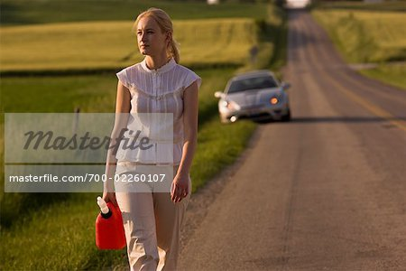 Woman Walking Along Country Road, Carrying Gas Can Stock Photo - Rights-Managed, Image code: 700-02260107