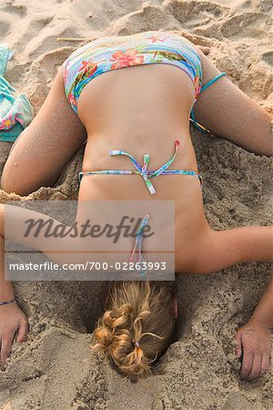 Teenaged Girl Sticking Head Into Hole in the Sand Stock Photo - Rights-Managed, Image code: 700-02263993