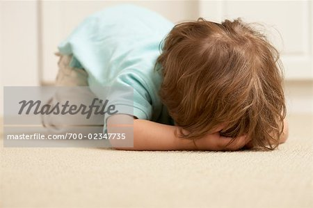 Boy on Floor with Face Covered Stock Photo - Rights-Managed, Image code: 700-02347735