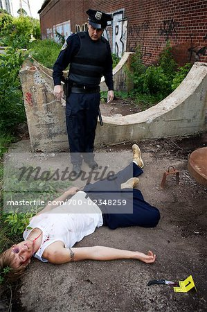 Police Officer with Dead Body at Crime Scene, Toronto, Ontario, Canada