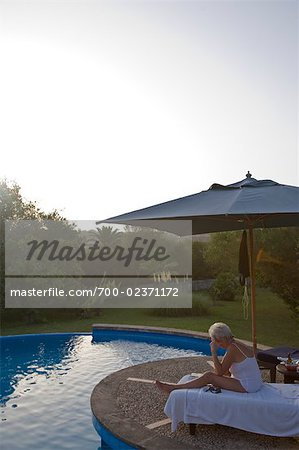 Woman Relaxing by Swimming Pool at Dusk, Mallorca, Baleares, Spain Stock Photo - Rights-Managed, Image code: 700-02371172