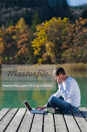 Man Sitting on Dock, Talking on Cell Phone and Using Laptop, Fuschlsee, Fuschl am See, Salzburger Land, Austria Stock Photo - Rights-Managed, Image code: 700-02428742