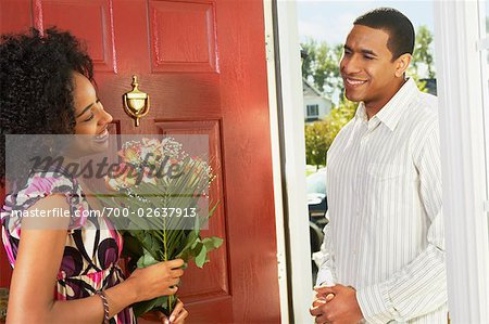 Woman Receiving Flowers from Man in Doorway Stock Photo - Rights-Managed, Image code: 700-02637913